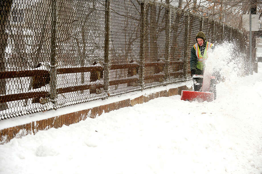 Hour photo / Erik Trautmann DPW employee Neil Dennehy throws snow from the sidewalks on the I-95 overpass on Strawberry Hill Ave as Norwalkers cope with the blizzard that hit the Northeast Tuesday.
