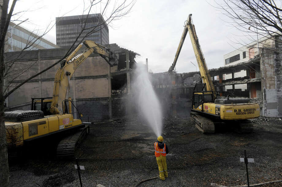 In this Dec. 18, 2014 photo, a wrecking company worker sprays water to keep dust down as heavy machinery tears down a 1960s-era parking garage in downtown Asheville, N.C. A developer will begin constructing a nine-story, upscale hotel with retail along the street _ circling back to what was there before the '60s. Communities across the country are demolishing the garages and putting up buildings again, confident that more people will be drawn to lively offices, hotels and housing. (AP Photo/The Citizen-Times, William Woody)