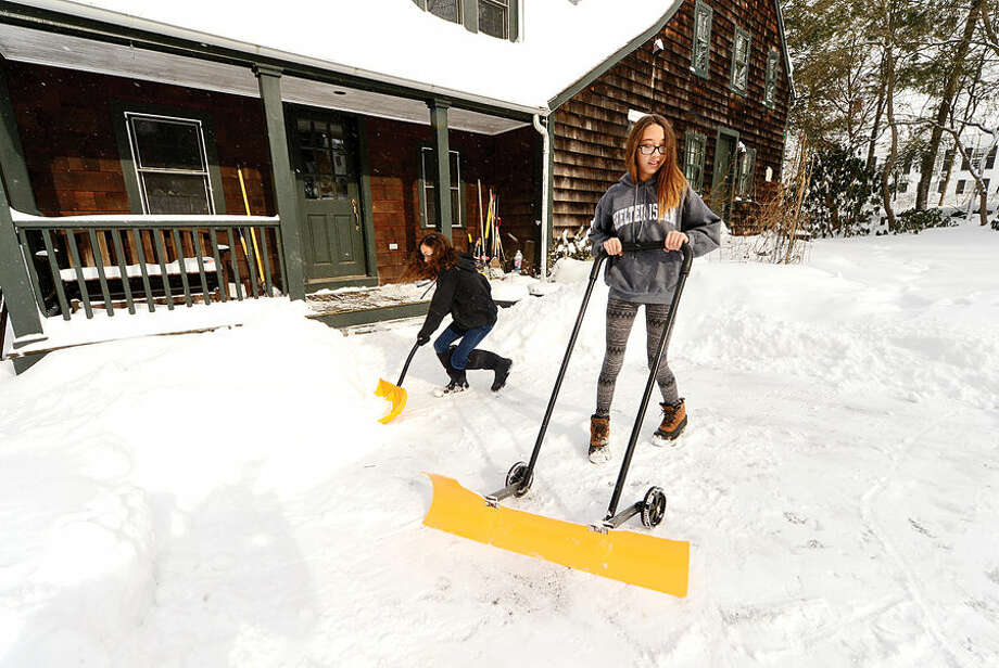Hour photo / Erik Trautmann Baily Foltz, 13 and her sister Merrin Foltz, 12, help shovel their driveway off Ridgefield Rd in Wilton after the blizzard that hit the area Tuesday.