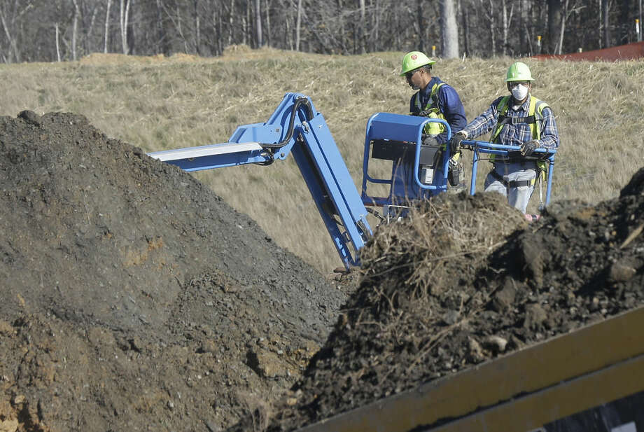 In this Thursday, Jan. 14, 2016, photo, workers excavate coal ash-laden soil to be removed from the Dan River Steam Station in Eden, N.C. Duke Energy Corp. is digging up and hauling away from riverbanks the toxic coal residues two years after one of the worst coal-ash spills in U.S. history. (AP Photo/Gerry Broome)