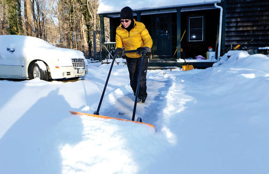 Isabel Foltz clears her driveway in Wilton of snow following the snowstorm Tuesday that dumped several inches in the area.
