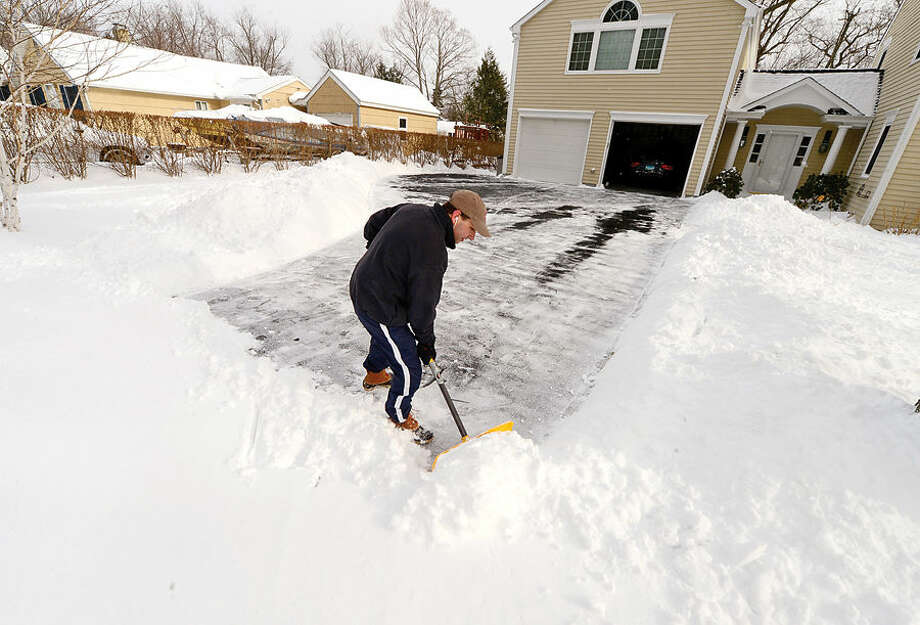 Hour photo / Erik Trautmann State Senate majority leader Bob Duff shovels his driveway after the blizzard that hit the area Tuesday.