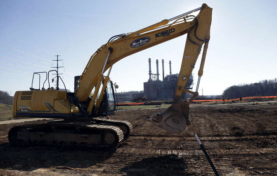 In this Thursday, Jan. 14, 2016, photo, heavy equipment excavates soil around the decommissioned Dan River coal-fired power plant at the Dan River Steam Station in Eden, N.C. Duke Energy Corp. is digging up and hauling away from riverbanks the toxic coal residues two years after one of the worst coal-ash spills in U.S. history. (AP Photo/Gerry Broome)
