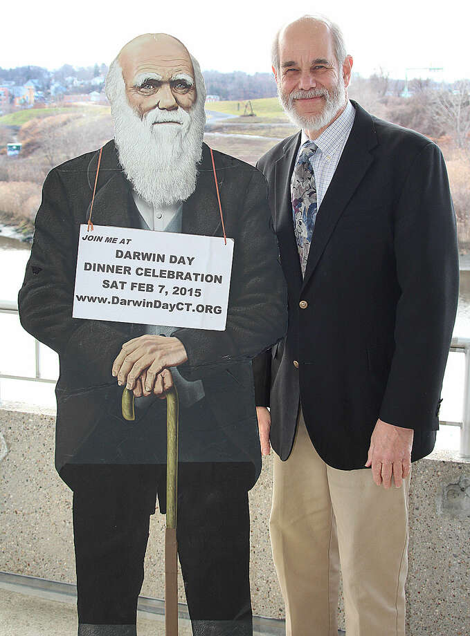 Hour photo/Chris Bosak Cary Shaw, one of the organizers of the upcoming Darwin Day Dinner Celebration, stands next to a life-sized cutout of Charles Darwin.