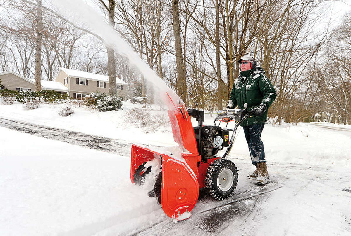 Hour photo / Erik Trautmann John Weidner throws snow from his driveway on Salem Rd in Wilton after the blizzard that hit the area Tuesday.