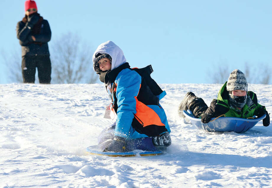 Hour photo / Erik TrautmannChristian Miller, 11, and Colin Lenskold, 10, sled at Nathan Hale Middle School following the snowstorm that left the area blanketed with snow and canceled public school in Norwalk Wednesday.