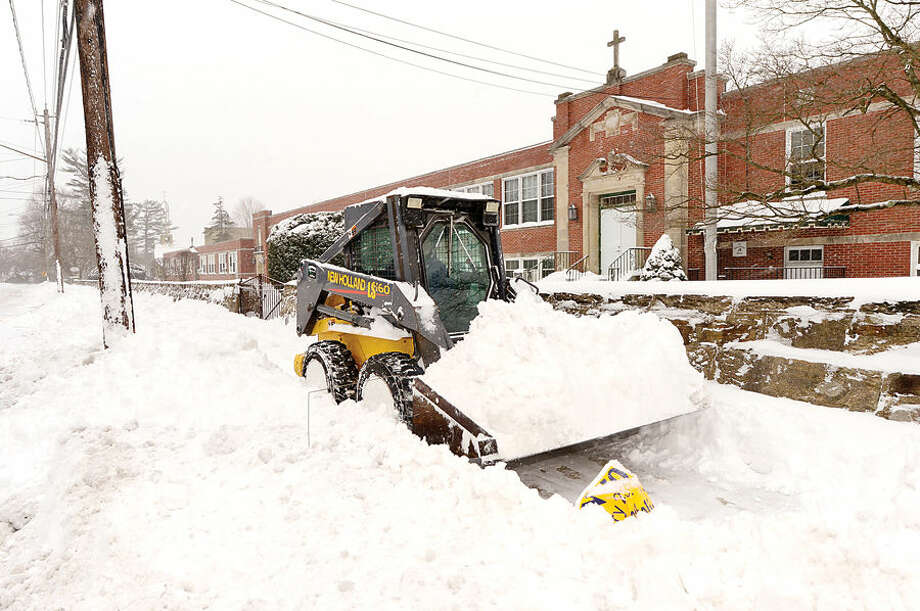 Hour photo / Erik Trautmann Rick Lusardo of Grounds management plows the sidewalk at St. Philip's Church as Norwalkers cope with the blizzard that hit the Northeast Tuesday.