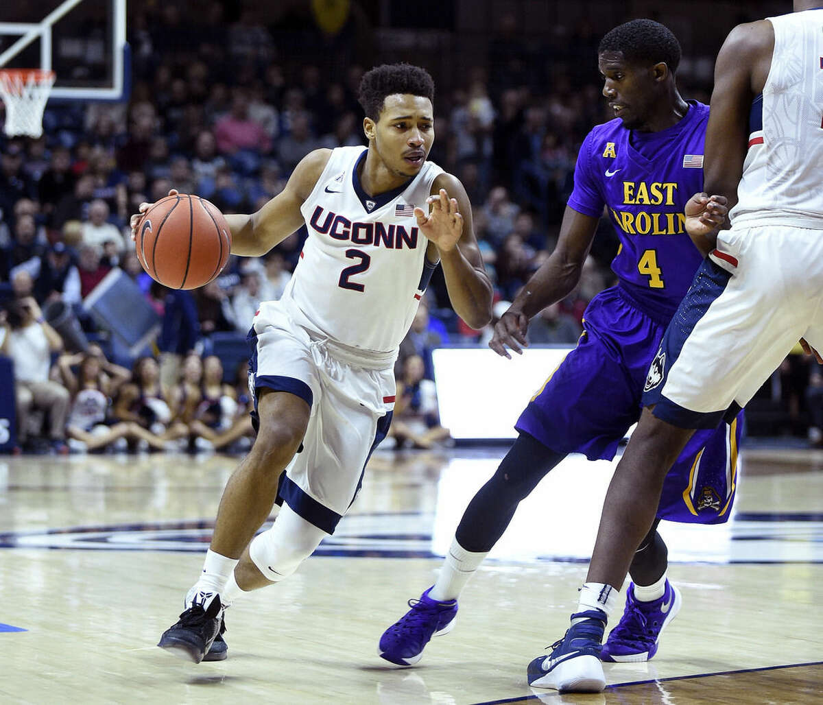 Connecticut's Jalen Adams (2) drives past East Carolina's Prince Williams (4) during the first half of an NCAA college basketball game in Storrs, Conn., on Sunday, Feb. 7, 2016. (AP Photo/Fred Beckham)