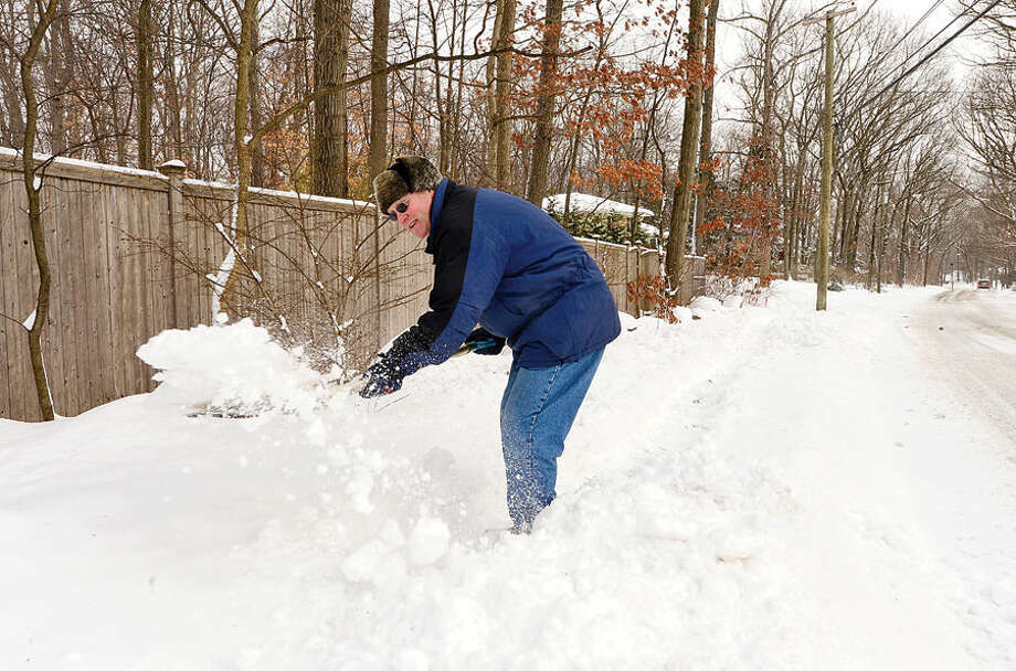 Hour photo / Erik Trautmann Mike Davey shovels a path for his daughter to get the her bus stop on Bayne St following the blizzard that hit the area Tuesday.