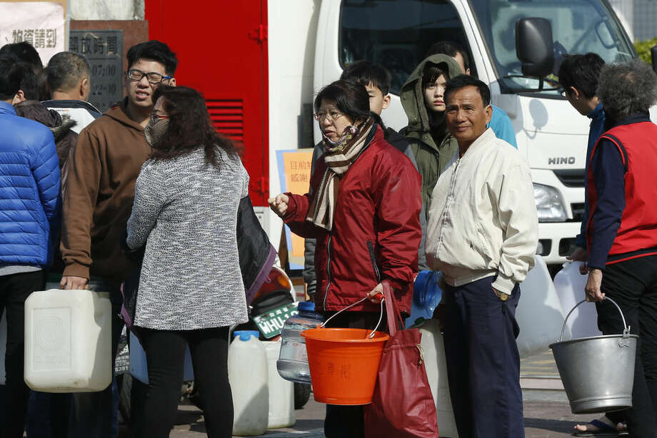 Local residents line up for potable water after being without since Saturday's earthquake in Tainan, Taiwan, Sunday, Feb. 7, 2016. Rescuers on Sunday found signs of live within the remains of a high-rise residential building that collapsed in a powerful, shallow earthquake in southern Taiwan that killed over a dozen people and injured hundreds. (AP Photo/Wally Santana)