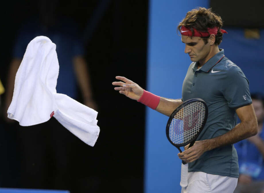 Roger Federer of Switzerland throws a towel as he plays Andy Murray of Britain during their quarterfinal at the Australian Open tennis championship in Melbourne, Australia, Wednesday, Jan. 22, 2014.(AP Photo/Rick Rycroft)