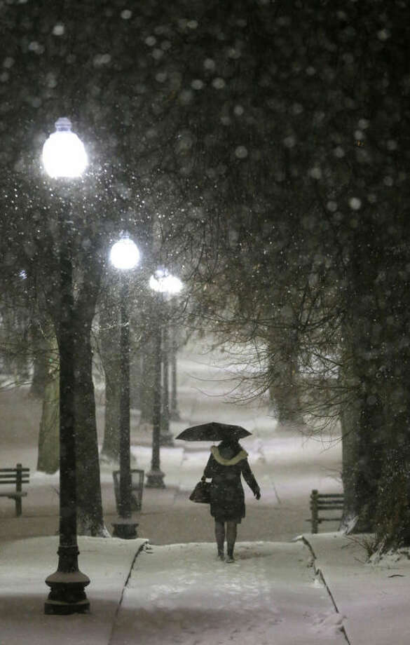 A woman uses an umbrella while walking along a snow-covered path in the Boston Common park, Tuesday, Jan. 21, 2014, in Boston. Heavy snow has been forecast and a blizzard warning was posted for portions of Massachusetts Tuesday, prompting Gov. Deval Patrick to dismiss nonemergency state workers early and postpone his annual State of the State address. (AP Photo/Steven Senne)