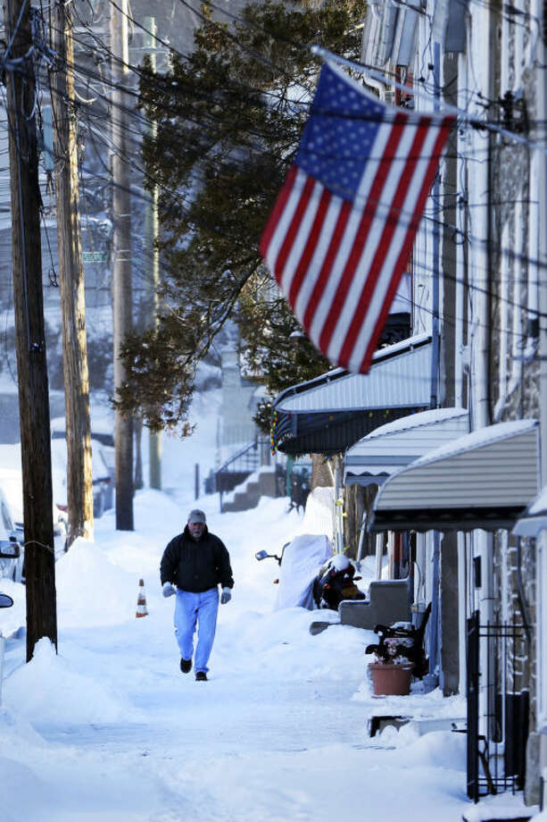 A man walks on an unsolved sidewalk in the aftermath of a snowstorm Wednesday, Jan. 22, 2014, in Philadelphia. A winter storm stretched from Kentucky to New England and hit hardest along the heavily populated Interstate 95 corridor between Philadelphia and Boston. (AP Photo/Matt Rourke)