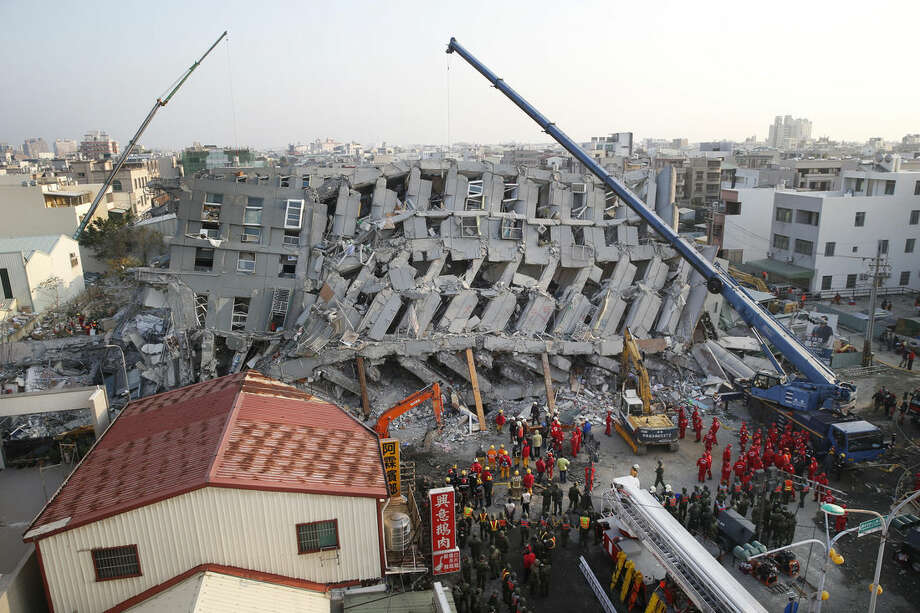 In the early morning, emergency rescuers continue to search for the missing in a collapsed building from an earthquake in Tainan, Taiwan, Sunday, Feb. 7, 2016. Rescuers on Sunday found signs of live within the remains of the high-rise residential building that collapsed in a powerful, shallow earthquake in southern Taiwan that killed over a dozen people and injured hundreds. (AP Photo/Wally Santana)