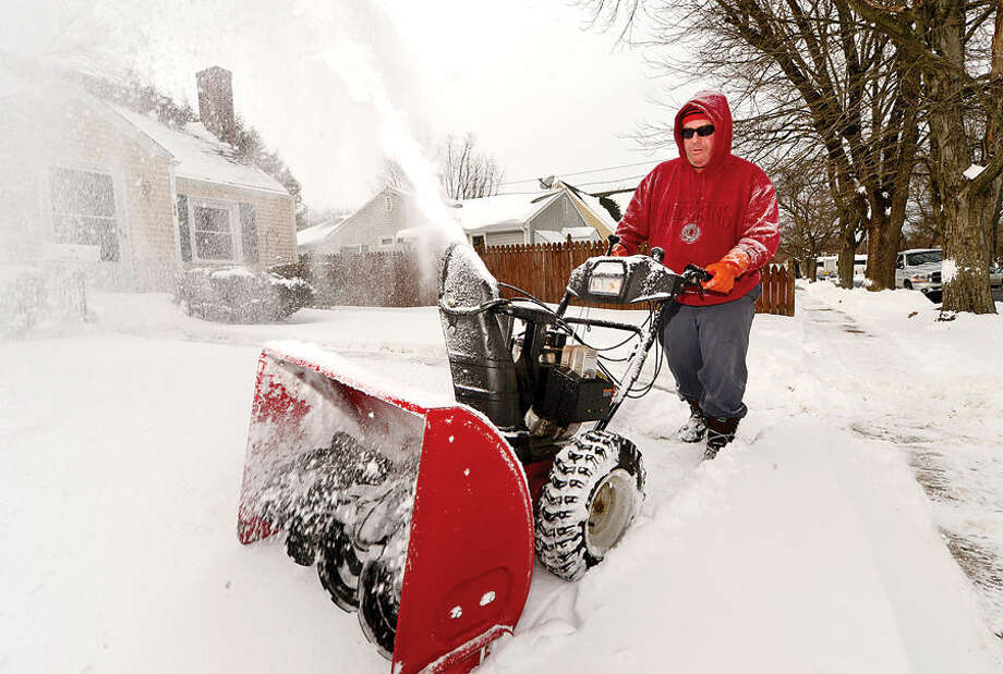 Hour photo / Erik Trautmann John Breen blows snow from the sidewalk in front of his home on Courtland Hill Ave in Stamford following the blizzard that hit the area Tuesday.