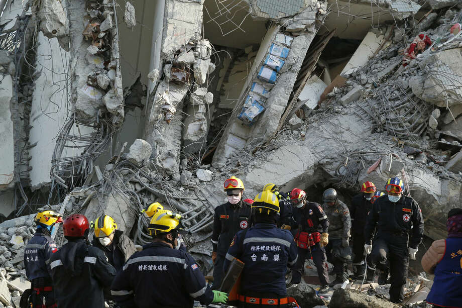 Standing below a beam of exposed oil cans used to fill space in some structures, rescuers continue to search for the missing in a collapsed building from an earthquake in Tainan, Taiwan, Sunday, Feb. 7, 2016. Rescuers on Sunday found signs of live within the remains of the high-rise residential building that collapsed in a powerful, shallow earthquake in southern Taiwan that killed over a dozen people and injured hundreds. (AP Photo/Wally Santana)