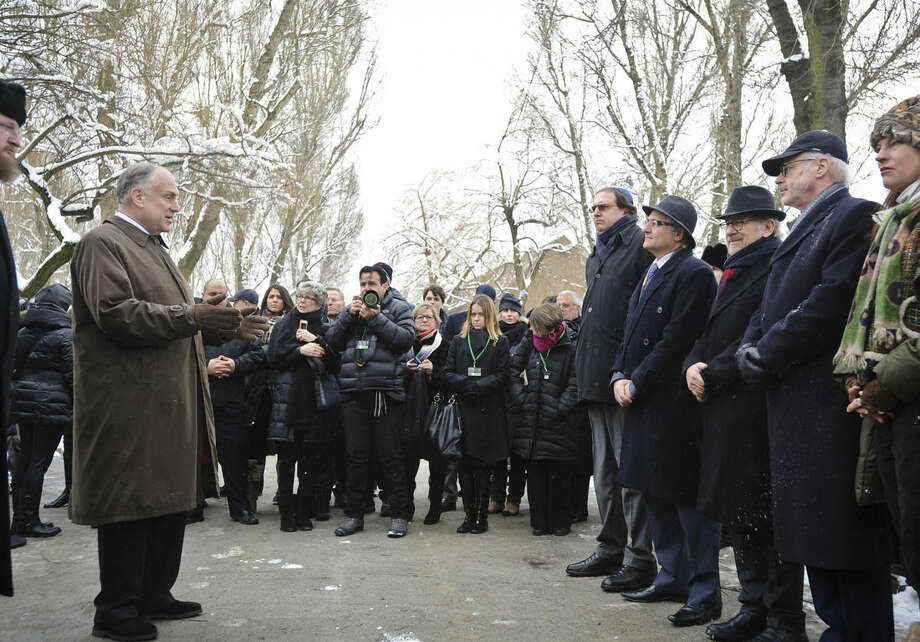 US film director Steven Spielberg, third from right, attends the unveiling of a memorial plaque as Ronald Lauder, President of the World Jewish Congress, left, speaks, at the Auschwitz Nazi death camp in Oswiecim, Poland, Tuesday, Jan. 27, 2015. Some 300 Holocaust survivors traveled to Auschwitz for the 70th anniversary of the death camp's liberation by the Soviet Red Army in 1945, down from 1,500 who attended the event 10 years ago.(AP Photo/Alik Keplicz)
