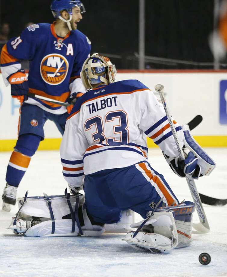 New York Islanders center Frans Nielsen (51), of Denmark, looks back as the puck rolls out of the crease behind Edmonton Oilers goalie Cam Talbot (33) after Islanders' Kyle Okposo (not shown) scored in the second period of an NHL hockey game in New York, Sunday, Feb. 7, 2016. (AP Photo/Kathy Willens)