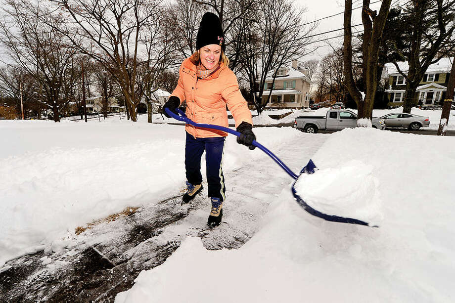 Hour photo / Erik Trautmann Terri Drew shovels her walk on Tremont Ave in Stamford following the blizzard that hit the area Tuesday.