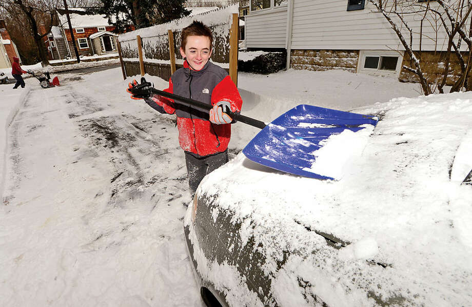 Hour photo / Erik Trautmann Owen Breen, 12, cleans off his parents car at their home on Courtland Hill Ave in Stamford following the blizzard that hit the area Tuesday.