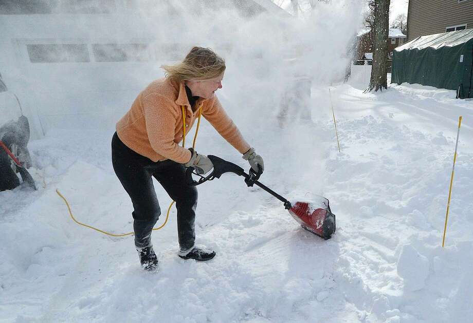 Hour Photo/Alex von Kleydorff Marjorie Madder uses a small snow blower along with a shovel to clear her drive on Vail St in Broad River on Tuesday
