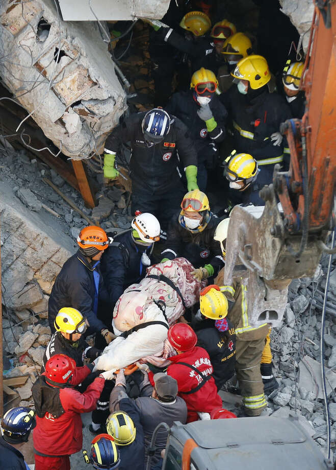 Emergency rescuers remove a body found in a collapsed building from an earthquake in Tainan, Taiwan, Sunday, Feb. 7, 2016. Rescuers on Sunday found signs of live within the remains of the high-rise residential building that collapsed in a powerful, shallow earthquake in southern Taiwan that killed over a dozen people and injured hundreds. (AP Photo/Wally Santana)