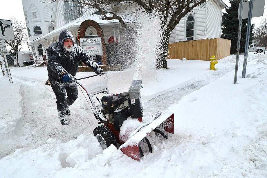 Hour Photo/Alex von Kleydorff Don Finch clears the sidewalks around The East Ave. Methodist Church on Tuesday morning, covered in snow from the blower, he is a member of the church and volunteers to help with clearing snow in the winter