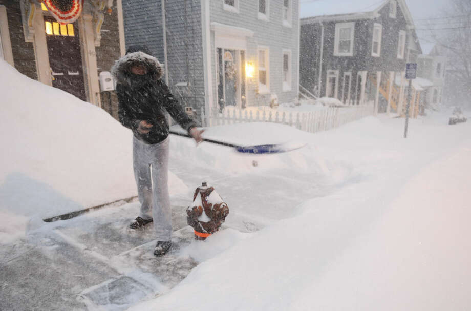 Shalonda Earvin clears the sidewalk in front of her Union St. home in Norwich, Conn., Tuesday, Jan. 27, 2015. Earvin said this was her fourth time out shoveling since it started snowing. (AP Photo/The Day, Sean D. Elliot)