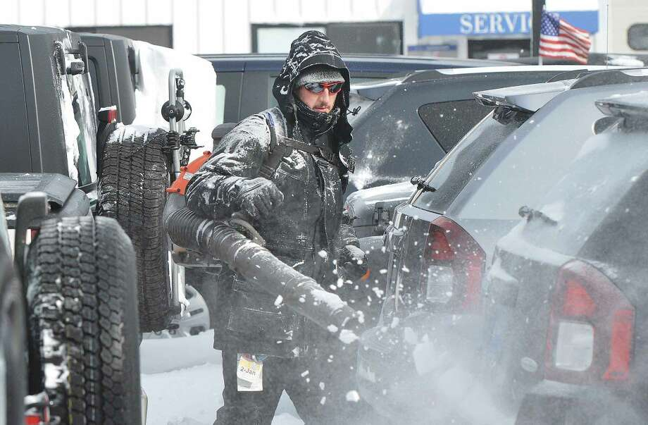 Hour Photo/Alex von Kleydorff Mike McGuire, Lot manager at Garavel Chrysler Jeep Dodge Ram uses a leaf blower to clear the snow from almost 300 cars before they are moved forward on the Westport Ave car dealerships lot