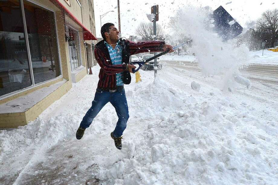 Hour Photo/Alex von Kleydorff Erick Khanau has some fun by trying to catch his thrown shovel full of snow while clearing the sidewalk in front of his store Harbor View Wine and Spirit on Main Ave Tuesday morning