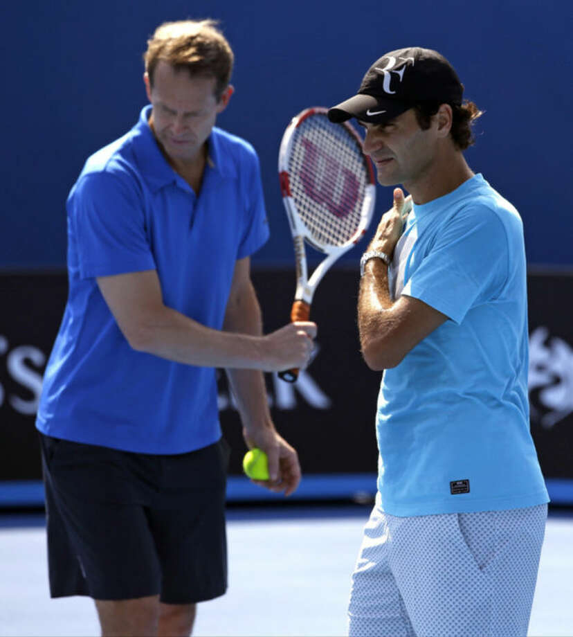 Switzerland's Roger Federer, right, practices along with his coach and former Grand Slam champion Stefan Edberg at the Australian Open tennis championship in Melbourne, Australia, Thursday, Jan. 23, 2014. Federer faces Rafael Nadal of Spain in the semifinal on Friday. (AP Photo/Aijaz Rahi)