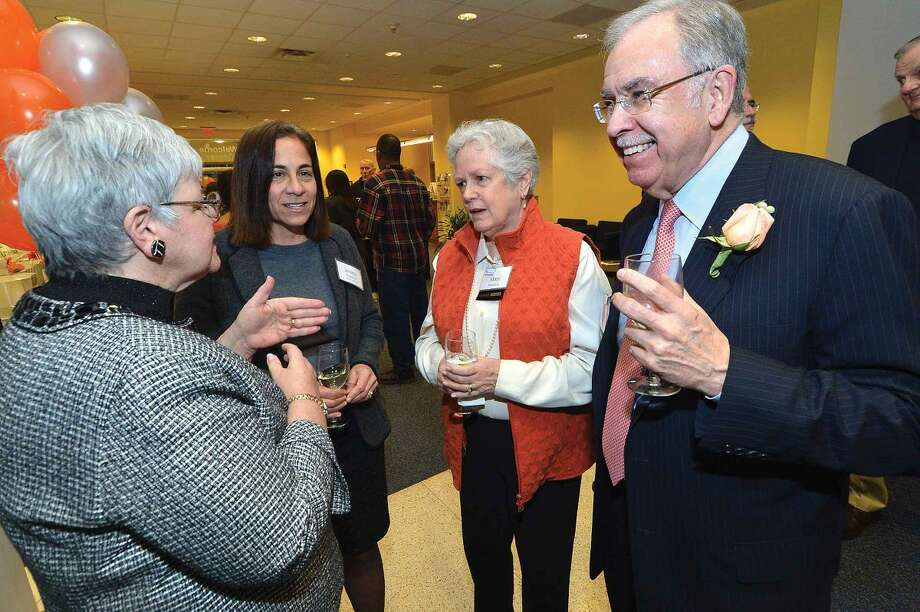 Don Case, chairman of SilverSources' board of directors, and his wife Patricia talk with Jevera Hennessey and Mary Maarbjerg during a reception at the University of Connecticut's Stamford campus.