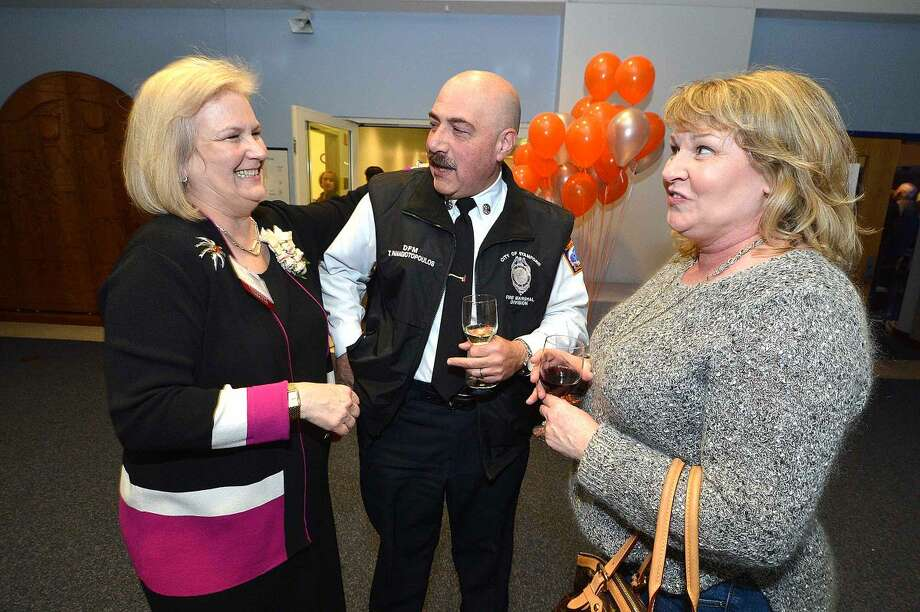 SilverSource Executive Director Kathleen Bordelon talks with Stamford Deputy Fire Marshal Ted Panagiotopoulos and his wife Jacky during a reception at the University of Connecticut's Stamford campus.