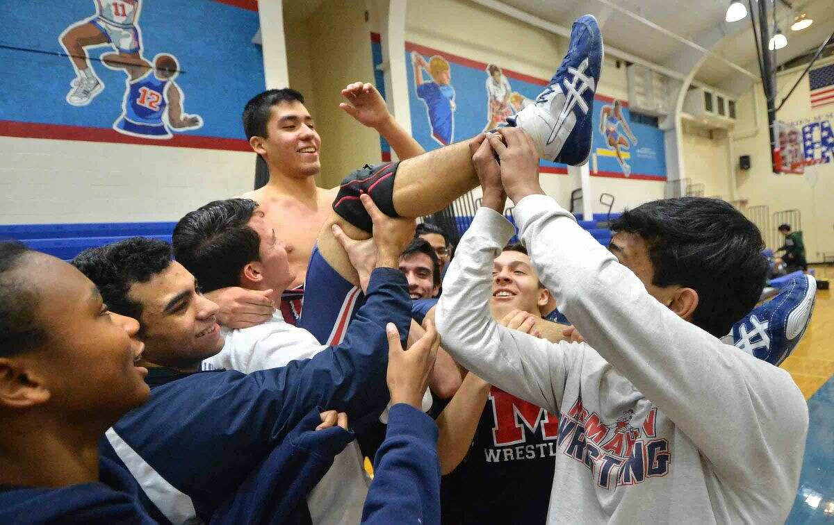 Hour Photo/Alex von Kleydorff Brien McMahons Aldo Ojeda is lifted by his teammates after he won his match vs Norwalk and McMahon took the win overall