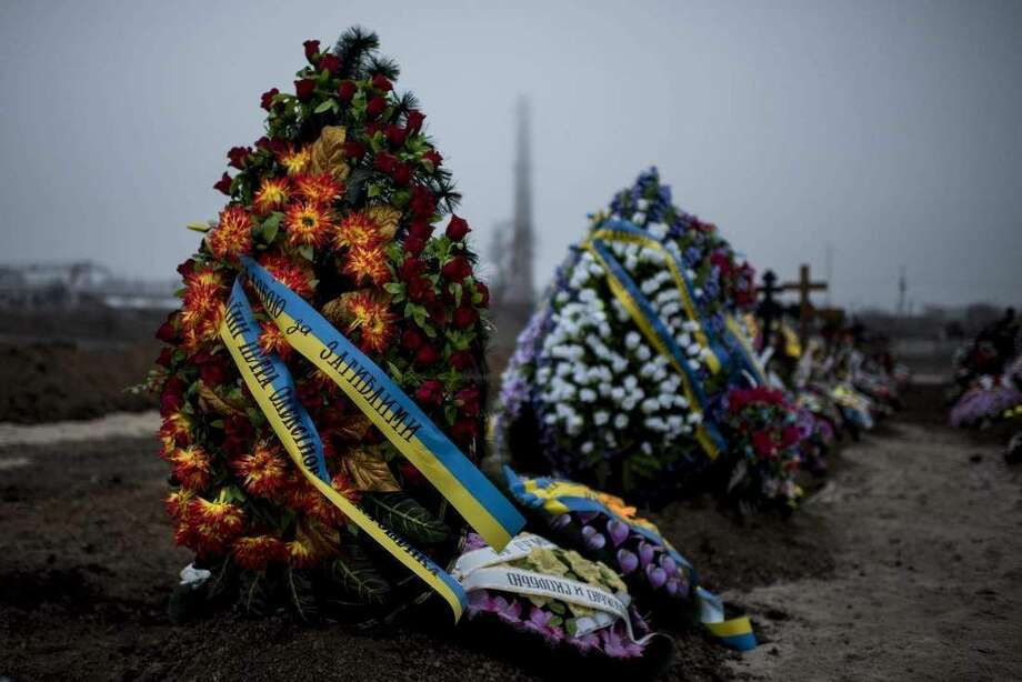 "Wreaths are placed on the graves of victims of Saturday's shelling after a funeral in Mariupol, Ukraine, Tuesday Jan. 27, 2015. European Union leaders are threatening fresh sanctions against Russia because of what it sees as ""growing support"" of Moscow for separatists in eastern Ukraine during intensified fighting over the past days. (AP Photo/Evgeniy Maloletka)"