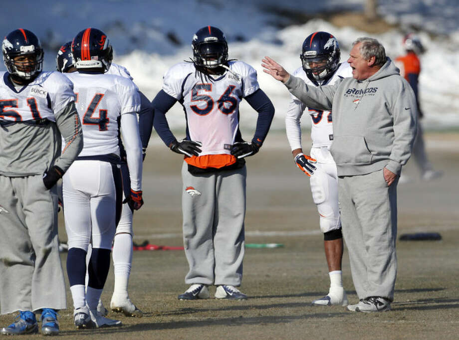 Denver Broncos linebackers coach Richard Smith, right, instructs his players during NFL football practice at the team's training facility in Englewood, Colo., on Thursday, Jan. 23, 2014. The Broncos are scheduled to play the Seattle Seahawks in Super Bowl XLVIII on Feb. 2. (AP Photo/Ed Andrieski)