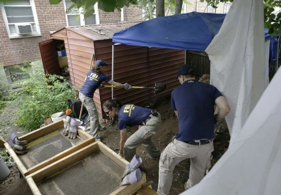 "FILE - In this June 18, 2013 file photo, FBI agents search the backyard of a house once occupied by James ""Jimmy the Gent"" Burke in New York. Burke masterminded a $5.8 million robbery from Lufthansa Airlines in 1978. Vincent Asaro, a mob associate of Burke's, was indicted, Thursday, Jan. 23, 2014 for participating in the armed robbery at Kennedy Airport. (AP Photo/Kathy Willens, File)"