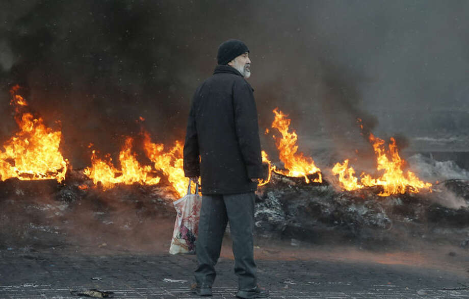 AP photo / Efrem LukatskyA Kiev resident looks at burning barricades between police and protesters in central Kiev, Ukraine Thursday. Thick black smoke from burning tires engulfed parts of downtown Kiev as an ultimatum issued by the opposition to the president to call early election or face street rage was set to expire with no sign of a compromise on Thursday.