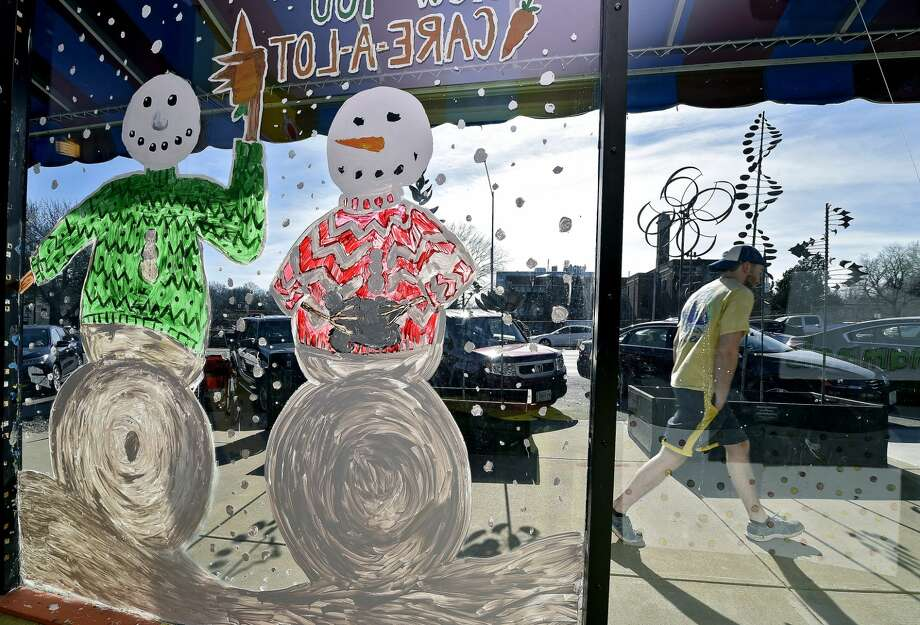 Michael Hilboldt heads to his car past the wintry storefront window of the Reading Reptile as warm weather continued on Wednesday, Jan. 28, 2015, in Kansas City, Mo. (AP Photo/The Kansas City Star, John Sleezer)