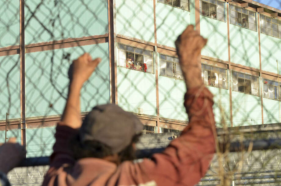 A man holds on to a fence surrounding the Topo Chico prison, where a riot broke out around midnight, in Monterrey, Mexico, Thursday, Feb. 11, 2016. Dozens of inmates were killed and several injured in a brutal fight between two rival factions at a prison in northern Mexico on Thursday, the state governor said. (AP Photo/Emilio Vazquez)