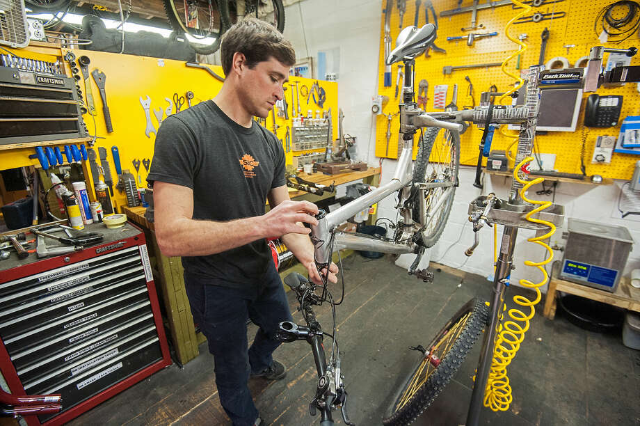 Shenandoah Bike Company service manager Collin Vento works on a customer's bike brought in for a winter overhaul in preparation for warmer weather in downtown Harrisonburg, Va., on Tuesday, Jan. 27, 2015. (AP Photo/Daily News-Record, Daniel Lin)