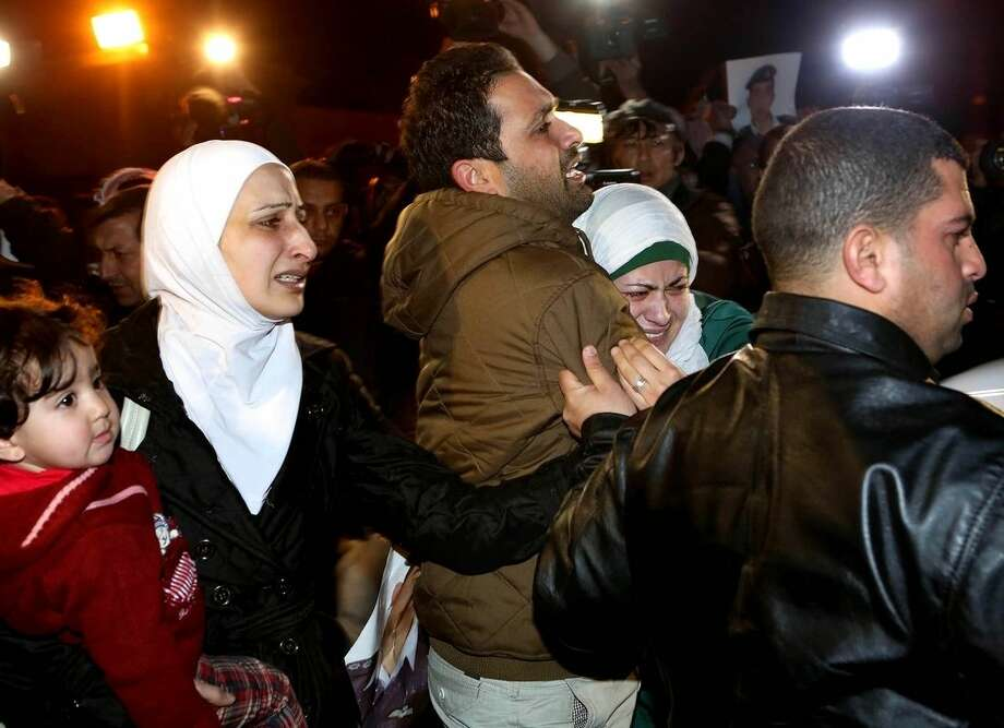 A man comforts the wife, right, of Jordanian pilot, Lt. Muath al-Kaseasbeh, who is held by the Islamic State group militants, during a protest in front of the Royal Palace in Amman, Jordan, Wednesday, Jan. 28, 2015. Jordan on Wednesday offered a precedent-setting prisoner swap to the Islamic State group in a desperate attempt to save a Jordanian air force pilot the militants purportedly threatened to kill, along with a Japanese hostage. (AP Photo/Raad Adayleh)
