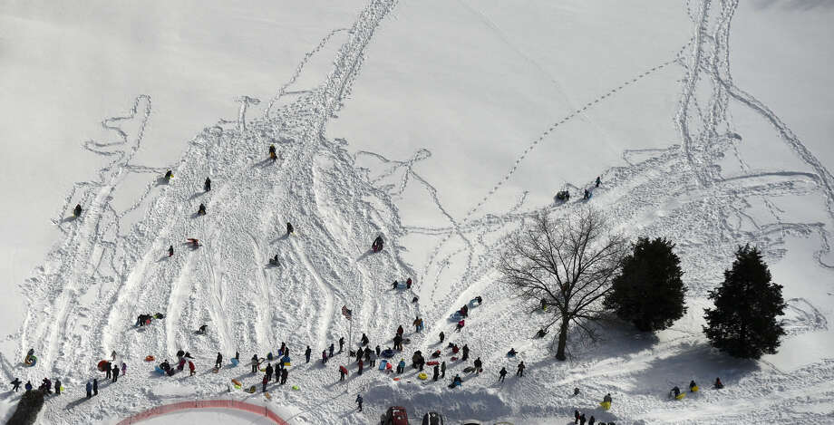 This aerial photo shows Sledders on a hill on the first hole fairway a golf course in Norwich, Conn., Wednesday, Jan. 28, 2015. (AP Photo/The Day, Sean D. Elliot) MANDATORY CREDIT