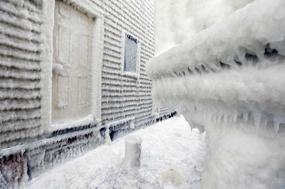 Frozen sea spray coats houses the day after a winter storm in Scituate, Mass., Wednesday, Jan. 28, 2015. Residents of Massachusetts woke up Wednesday to cars buried in several feet of snow, and secondary roads that remain covered. (AP Photo/Michael Dwyer)