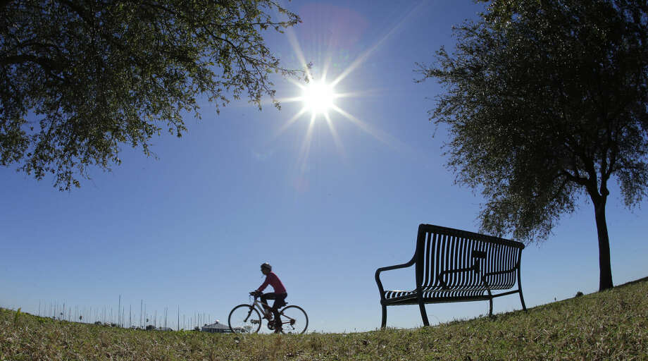 A cyclist takes advantage of the warm weather to ride along the Davis Islands yacht basin Tuesday, Jan. 27, 2015, in Tampa, Fla. A storm packing blizzard conditions spun up the East Coast early Tuesday, pounding parts of coastal New Jersey northward through Maine with high winds and heavy snow. (AP Photo/Chris O'Meara)