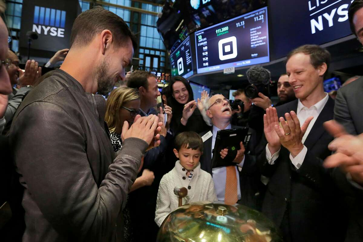 Mac Riley, center, son of Square CFO Sarah Friar, rings a ceremonial bell as the Square IPO begins trading, on the floor of the New York Stock Exchange, Thursday, Nov. 19, 2015. Flanking Riley are Square CEO Jack Dorsey, left, and co-founder Jim McKelvey, far right. Square, the 6-year-old startup known for its white, cube-shaped card readers that plug into smartphones, is surging in its first day as a publicly traded company. (AP Photo/Richard Drew)