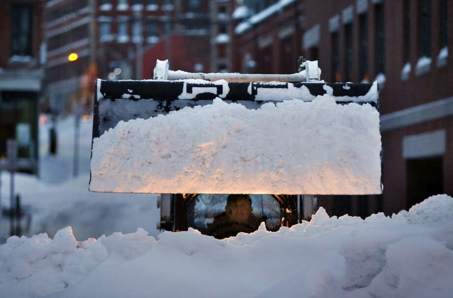 The driver of a front end loader prepares to dump a load of snow as Portland, Maine, digs out after a winter storm, Wednesday, Jan 28, 2015, in Portland, Maine. Tuesday's blizzard dumped about two feet of snow in Portland. (AP Photo/Robert F. Bukaty)