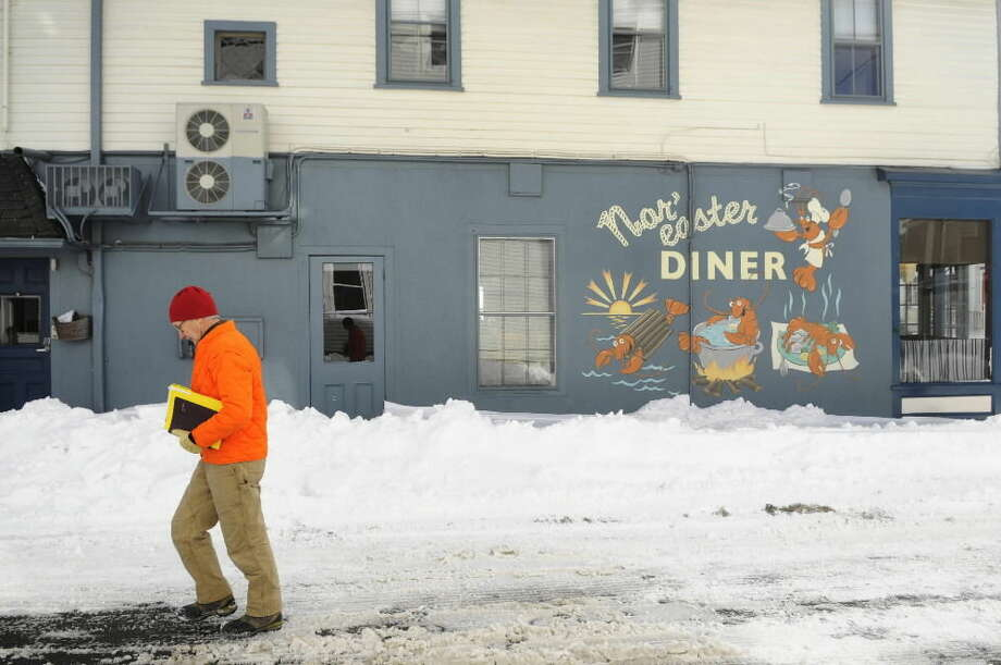 Jeff Callahan, Warden of the Borough of Stonington, walks in the snow after a winter storm, Wednesday, Jan. 28, 2015, in Stonington, Conn. The storm buried the Boston area in more than 2 feet of snow and lashed it with howling winds that exceeded 70 mph. (AP Photo/The Hartford Courant, Cloe Poisson)