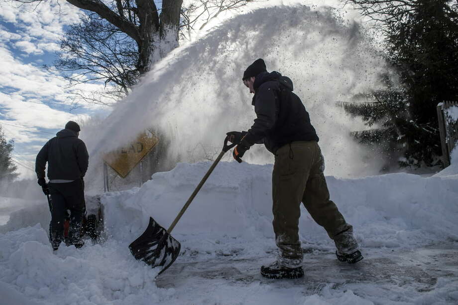 Joe Baton, left, and Austin Atlas clean a Mansfield sidewalk after a winter storm, Wednesday, Jan. 28, 2015, in Mansfield, Conn. The storm buried the Boston area in more than 2 feet of snow and lashed it with howling winds that exceeded 70 mph. (AP Photo/The Hartford Courant, Mark Mirko)