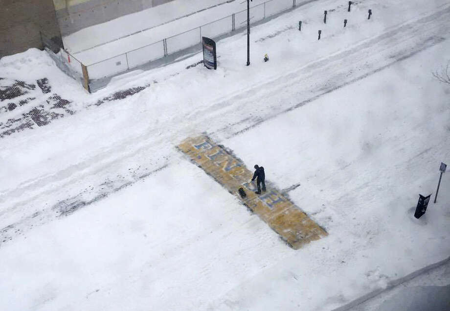 In this Tuesday, Jan. 27, 2015, photo, provided by Philip L. Hillman, Chris Laudani, a bartender at the Back Bay Social Club, shovels snow from the Boston Marathon finish line on Boylston Street, in Boston, during a winter storm that slammed eastern Massachusetts with as much as 2 feet of snow. (AP Photo/Philip L. Hillman)